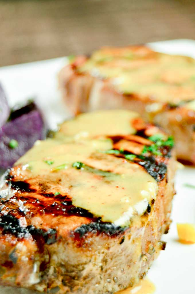 Grilled Pork chops on a white plate with mustard sauce over the top