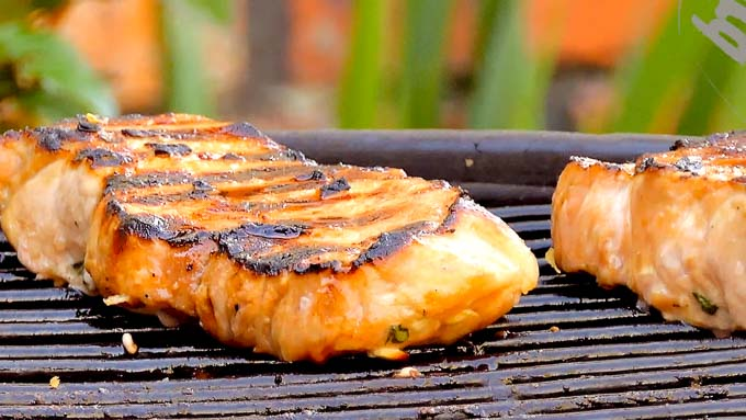 two boneless chops cooking on the grill