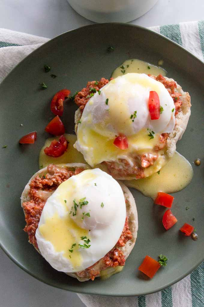 Italian Eggs Benedict served with tomatoes on a plate