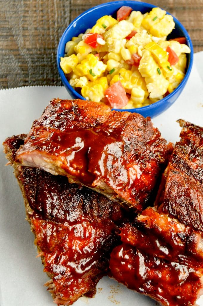 Ribs stacked on a white paper with corn in back