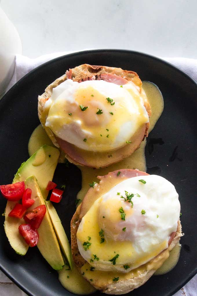 Two servings Classic Eggs Benediict with avocado and creamy hollandaise