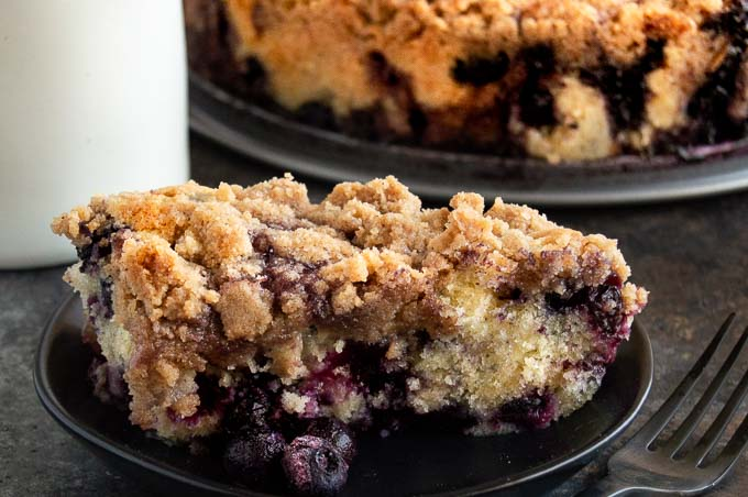 This Blueberry Buckle recipe is full of fresh juicy blueberries in a moist crumb cake that is topped with a crunchy sweet streusel for a bite of sweet, tart, moist and crunchy in every bit! Ideal for serving as a dessert or a breakfast cake!
