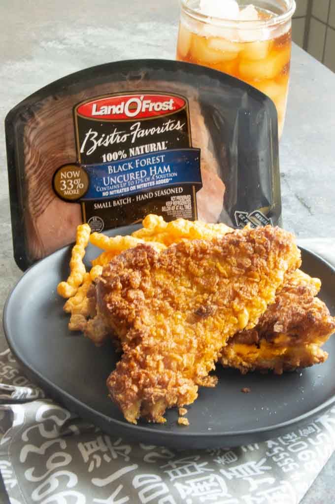 Cheese Frenchee on a plate in front of the Land O' Frost ham packaging