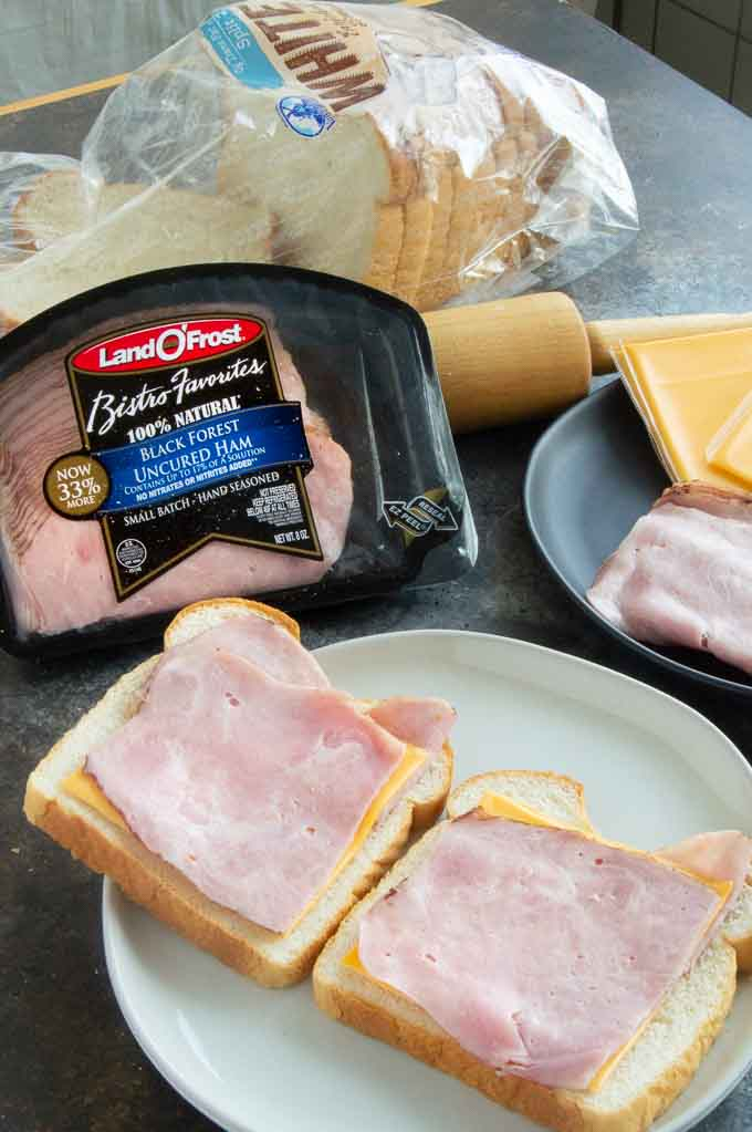 Preparing ham and cheese slices on the bread