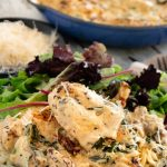 Creamy tuscan garlic chicken on the plate with a salad