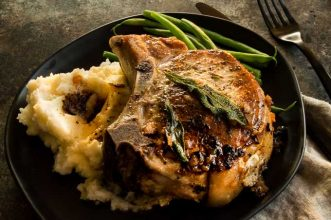 A dinner plat of Savory Baked Stuffed Pork chops are filled with hints of apples, mushrooms and creamy cheese.  Easy Gourmet meal to make for weeknight entertaining.  Perfect alternative to Thanksgiving turkey.