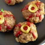 close up of halloween theme food meatballs that look like eyeballs