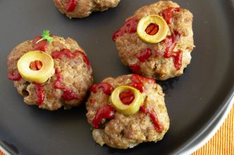 close up of halloween theme food meatballs that look like eyeballs