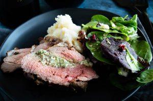 stuffed lamb roast on a black plate with potatoes and salad