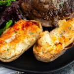 Twice baked potatoes are a fancy side dish that pair beautifully with any meal.  Crunchy tops with creamy, tangy potatoes underneath make this double baked potato a popular choice for special occasion steak dinners at home!