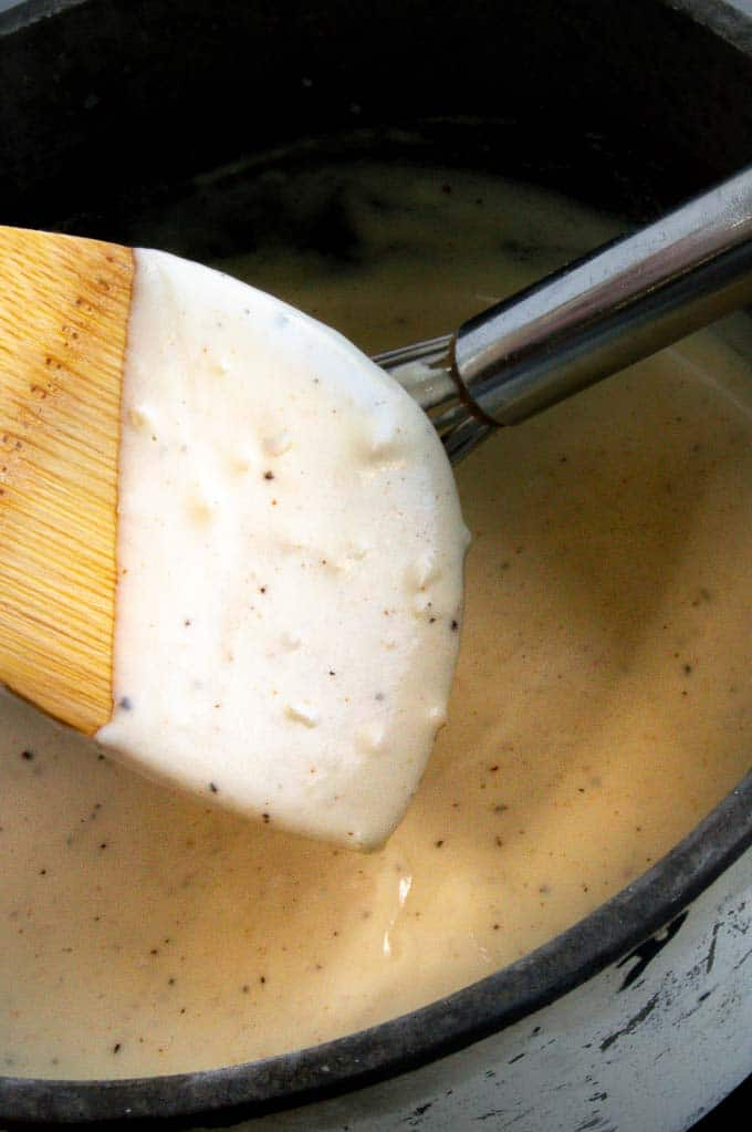 Showing thickness of cream sauce on a wooden spoon