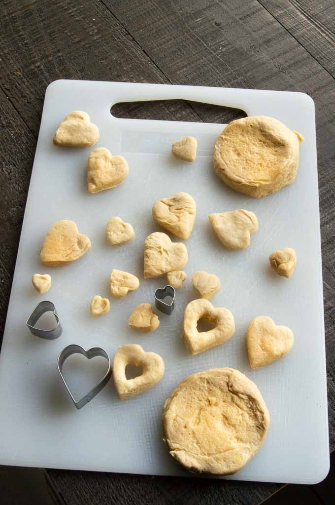 cutting the biscuit dough into hearts on a cutting board
