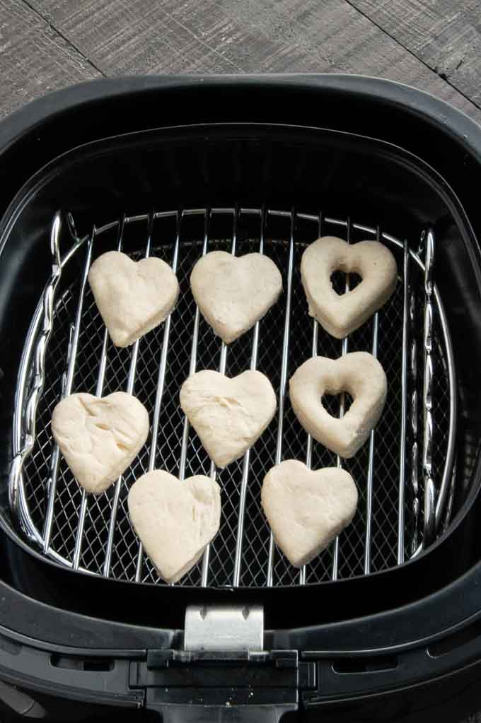 biscuit dough cut into hearts on the shelf of an air fryer