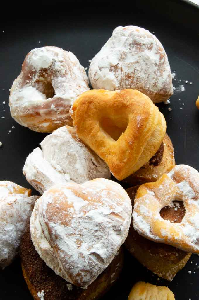 sugared heart shaped donuts on a black plate