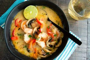 Serving bowl of thai soup with large shrimp and lime on top