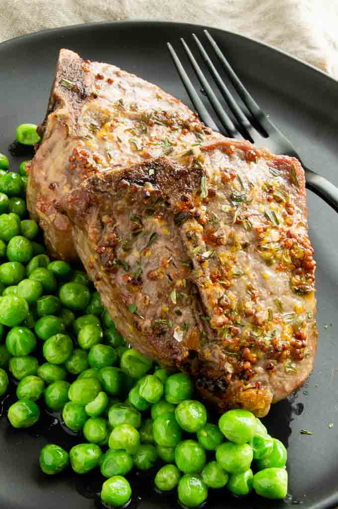 Marinated Lamb chops on a plate with peas.