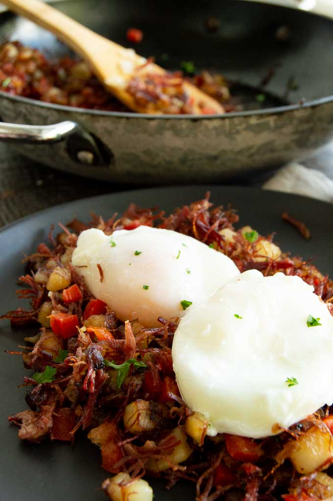 Serving hash with corned beet and eggs on a black plate
