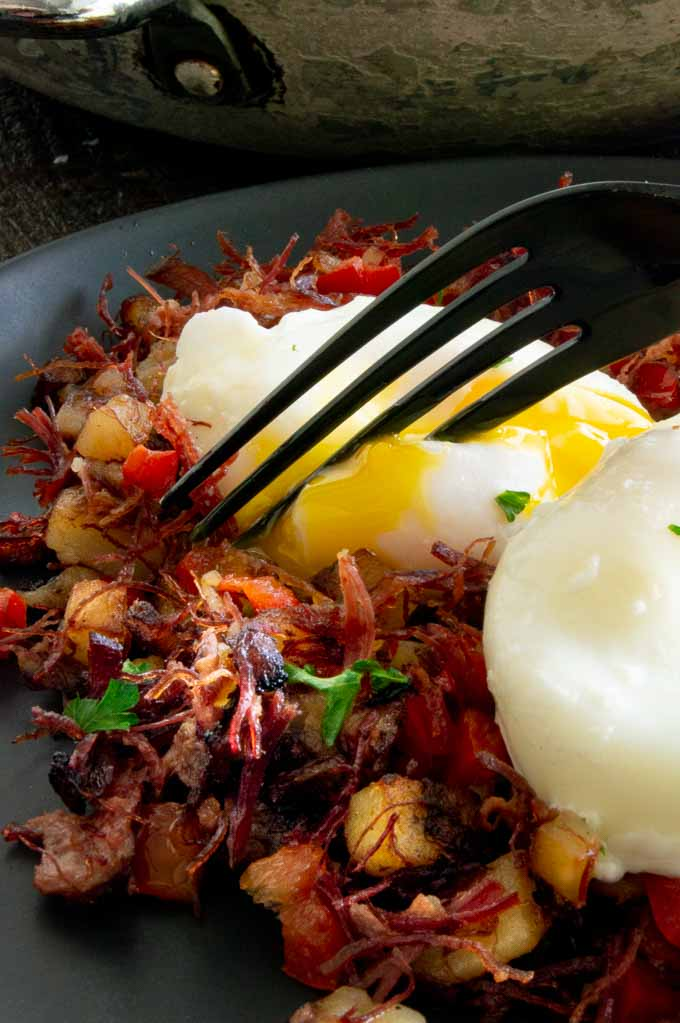Creamy egg yolk dripping over the top of the corned beef hash