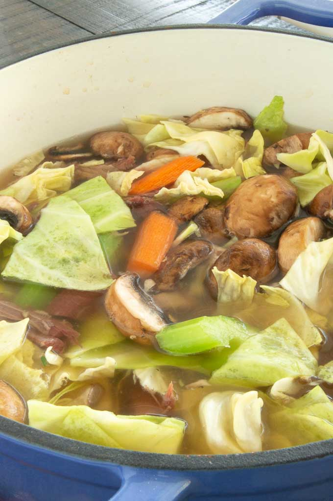 Leftover Corned Beef makes the most delicious Corned beef and Cabbage Soup.  Filled with cabbage, mushrooms, celery, carrots and onions surrounding big chunks of corned beef in a deep rich flavorful stew broth.  #corned beef #cornedbeefstew #leftover-cornedbeef #cornedbeefandcabbagerecipe #cornedbeefsoup