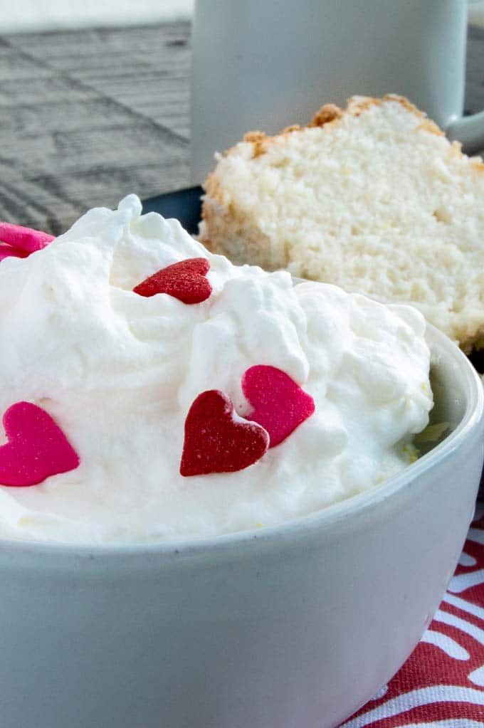 Heart candies on top of fresh whipped cream for dipping your angel food cake into.