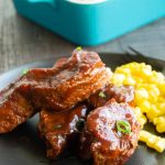 boneless pork ribs on a black plate with corn