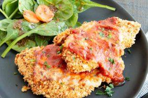 Marinara sauce over chicken parmesan on a plate