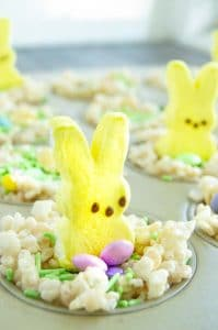 Peeps on top of Krispie treat nests in a pan