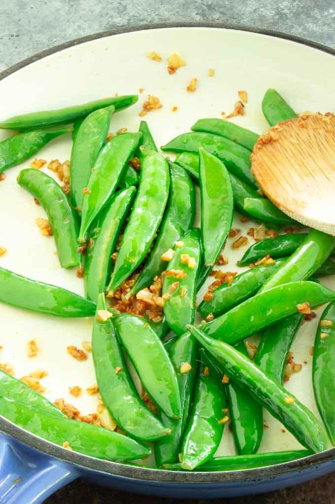 stir frying garlic and sugar snap peas