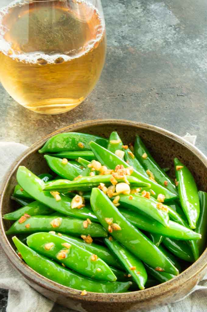 Serving bowl with fresh sugar snap peas and garlic