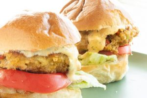 two crab cake on a bun with lettuce , tomato and sauce