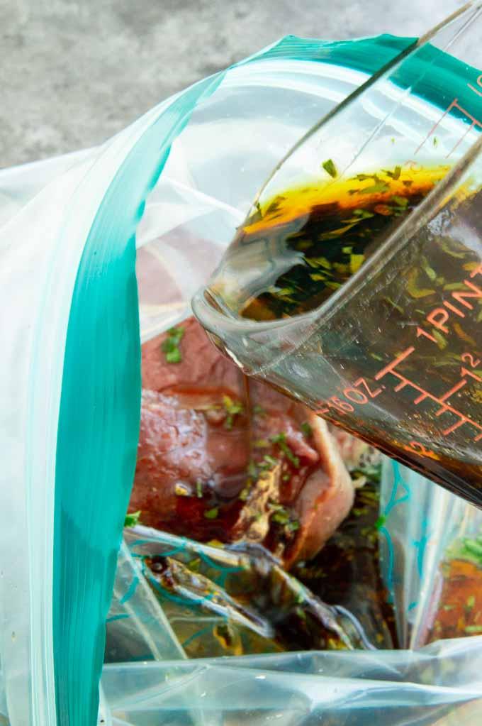pouring of dark liquid marinade into zip lock bag of Carne Asada