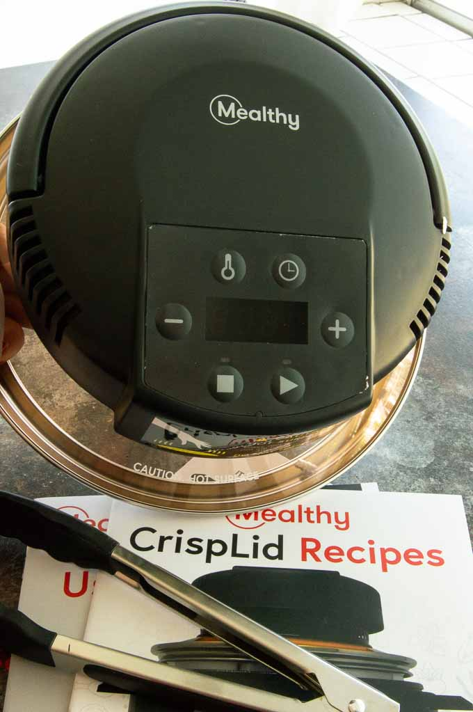 Mealthy Crisp Lid, tongs and recipe book on the table