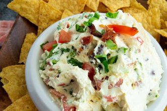 Fresh cream cheese dip with bacon lettuce and tomatoes inside and on top for serving.