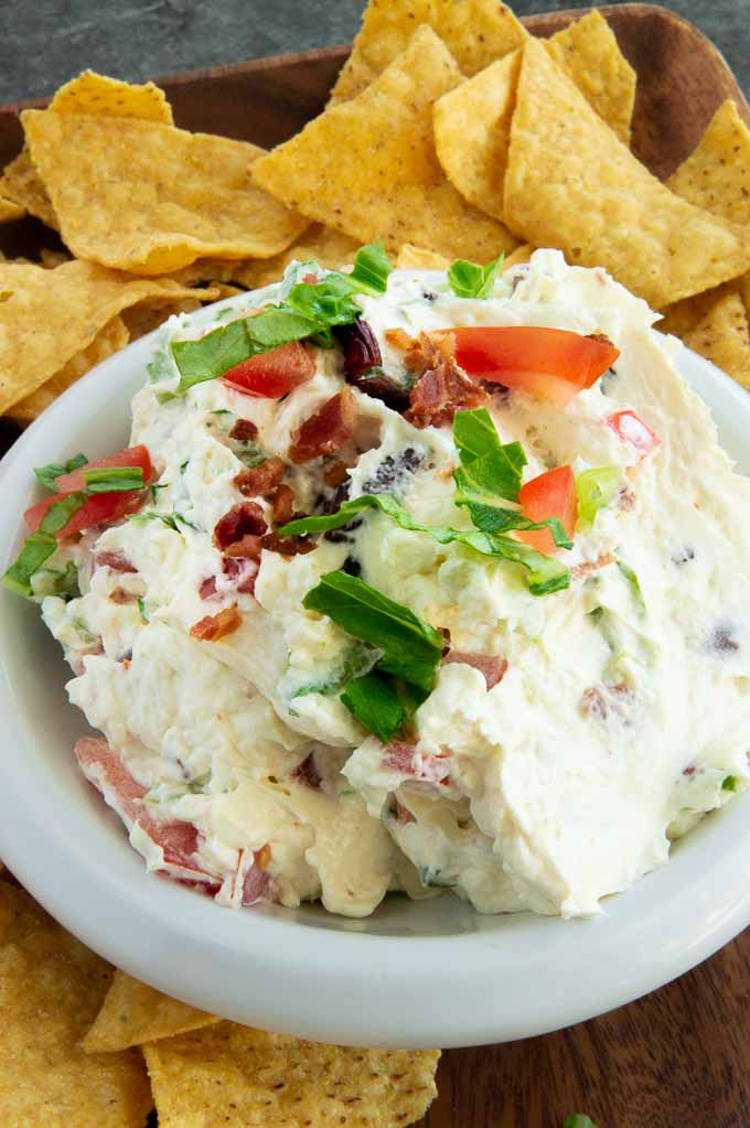BLT dip in a bowl with chips surrounding it.