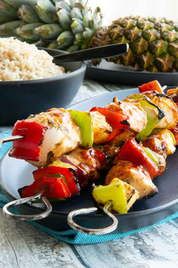 Serving platter of Hawaiian chicken kebobs on a buffet with rice and pineapple.