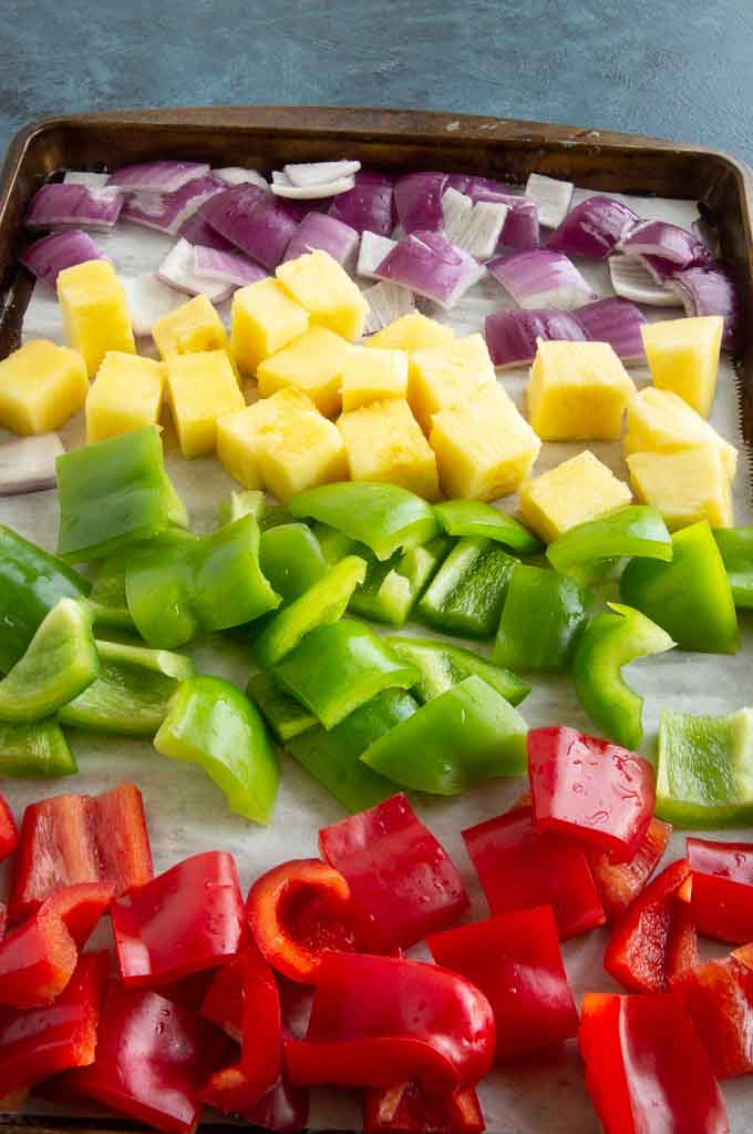 veggies and fruits for Hawaiian kebobs: green peppers, red peppers, pineapple chunks, red onions