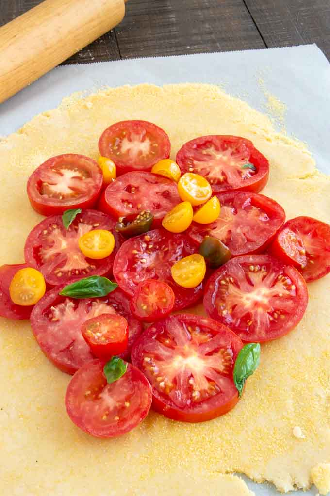 Putting the tomato slices for the tomato gullet in the center of the dough