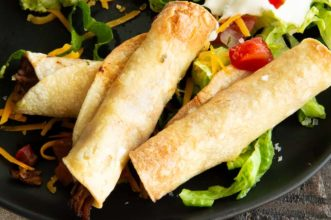 crispy taquitos on a black plate on a table