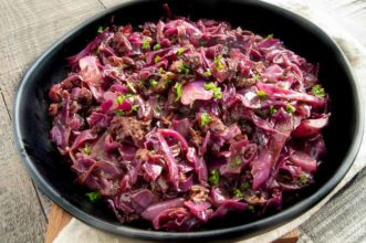 Serving table with a black bowl of braised red cabbage.