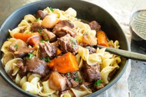 close up of Beef Bourguignon over noodles