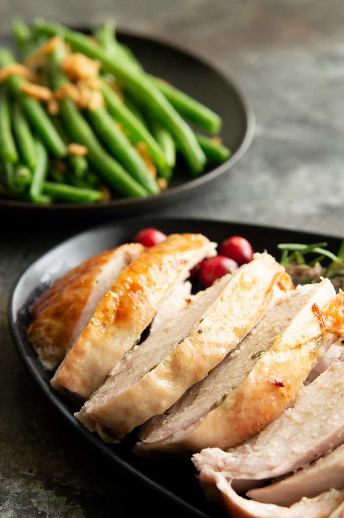 Sliced juicy turkey on a black plate with cranberries and green beans