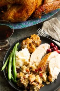 Sliced Juicy turkey with gravy, stuffing, beans and sweet potatoes.