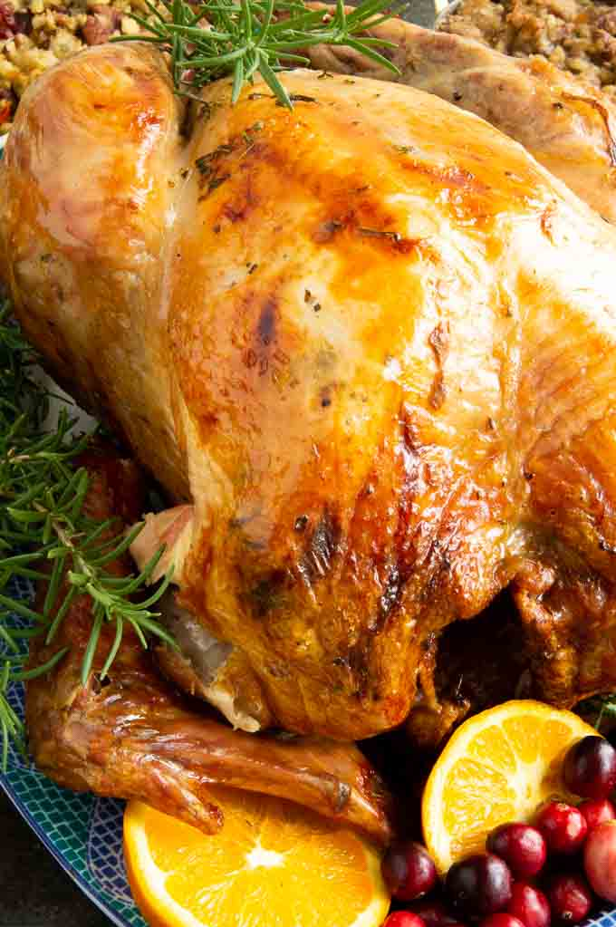crispy skin roasted turkey becomes the perfect golden color. Displayed on a black plate with cranberries and oranges.