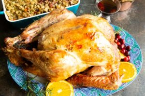 Perfectly golden oven roasted herb turkey on a serving platter