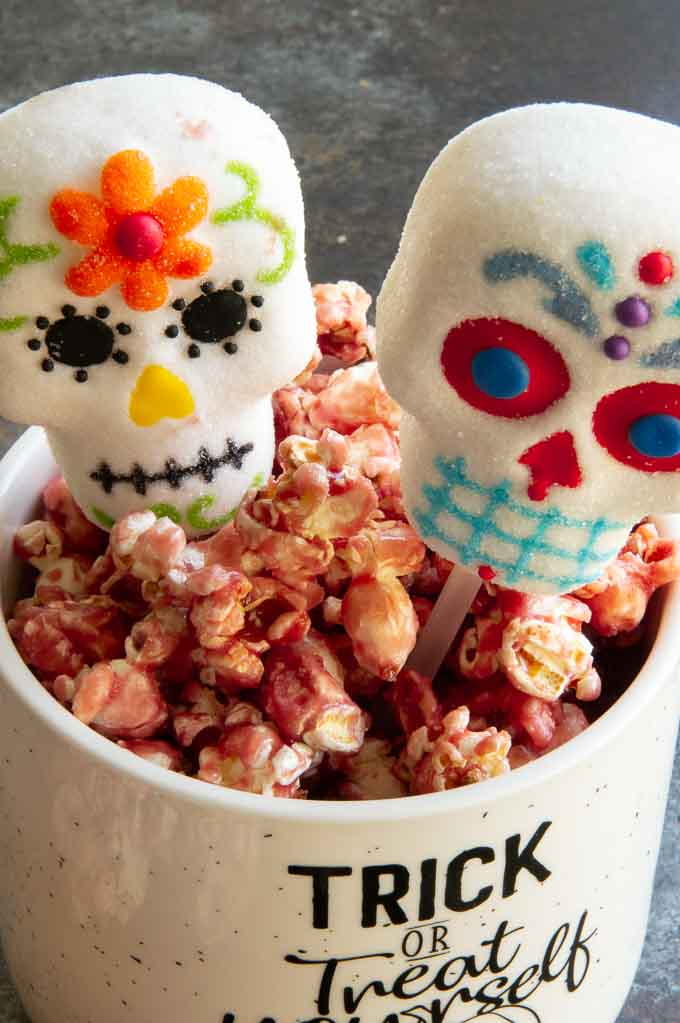 sugar skull marshmallows in a container of caramel popcorn.