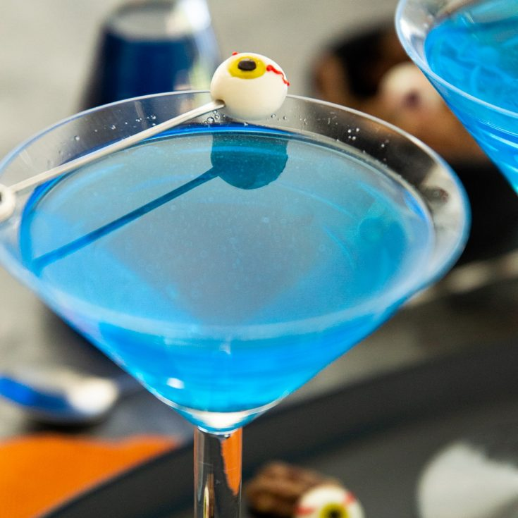 blue cocktail with an eyeball olive