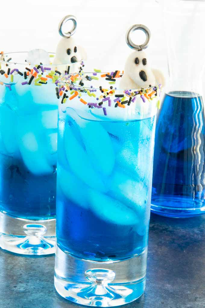 HIghball glasses with bright blue halloween cocktails