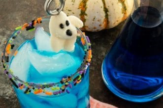 Sprinkle Edged Blue Blood Halloween cocktail with a Ghost canry