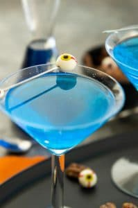 "Bright Blue Ghouls Blood Cocktail in martini galss with an eyeball ""olive"""