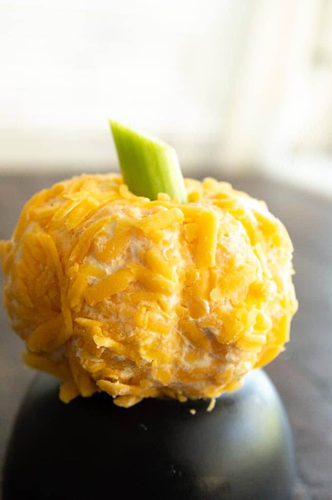 Pumpkin Shaped CHeeseball on a black plate